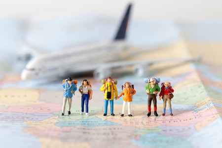 Miniature model team traveller model standing together on map, people travel in concept,