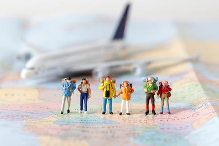 Model miniaturowego modelu podróżnego zespołu stojącego razem na mapie, ludzie podróżują w koncepcji, Zdjęcie Seryjne