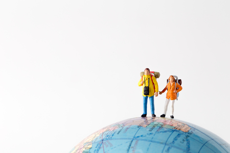 Miniature model couple traveller standing together, people travel in concept,  isolatrd on white background.
