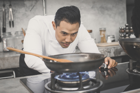 Mature chef in kitchen cooking dish for dinner , 30-40 year old, vintage tone. Stock Photo