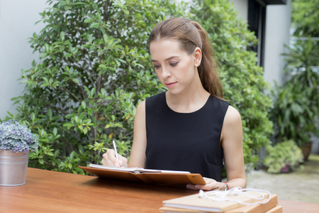 Portrait of a beautiful young woman reading book while driking coffee, 20-30 year old. Stock Photo