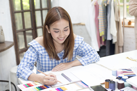 Young asian designer woman warking at studio. Fashion designer carefully creating new fashionable styles. Dressmaker makes clothes via additional part-time job. 版權商用圖片