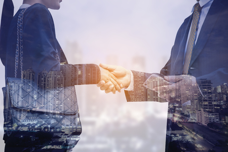 Double exposure of businesspeople shaking hand together with agreemant concept.