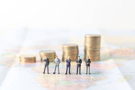 style advice: miniature model group of investor standing together on world map. Stock Photo