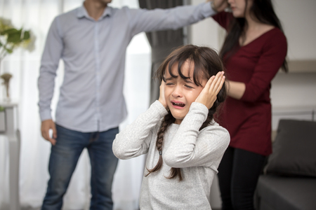 Little girl crying while parents quarrel. Closing the ears, 5-10 years old, family violence concept.