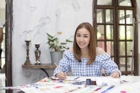 Young asian designer woman warking at studio. Fashion designer carefully creating new fashionable styles. Dressmaker makes clothes via additional part-time job. Stock Photo