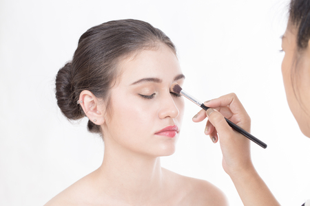 Makeup artist applies brushed at woman face. Beautiful woman face. Perfect makeup, isolated on white background, 20s year old. Stock Photo