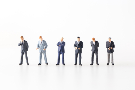 style advice: miniature model group of investor standing together isolated on white background.