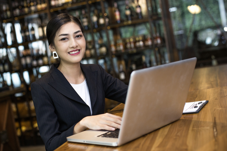 marketing online: Asian Woman using laptop in restaurant with Attractive Smiling, Woman working Concept