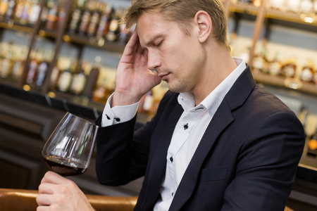pain: Businessman Hangover suffering when he drunk wine at Bat, Man with alcoholism concept.