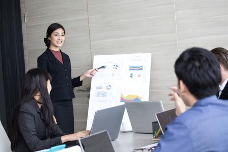 Mujer de negocios asiática que presenta su trabajo con el equipo en la sala de reuniones, gente que trabaja concepto. Foto de archivo