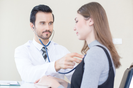 Doctor using stethoscope for listening woman. People with medical concept. Stock Photo