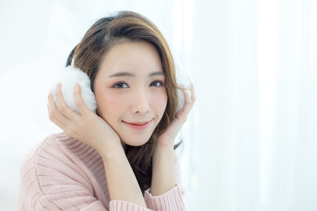 Attractive Asian Girl wearing sweater listen music with smile at home. Woman with winter concept.