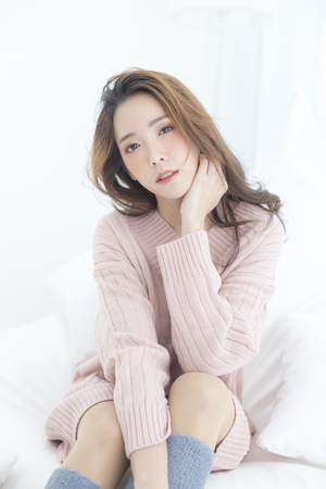 Asian Woman wake up on bed with happy emotion, People lifestyle concept.