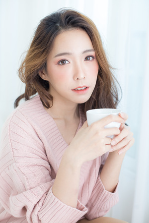 Asian Woman holding coffee cup at bedroom. People lifestyle concept. 스톡 콘텐츠