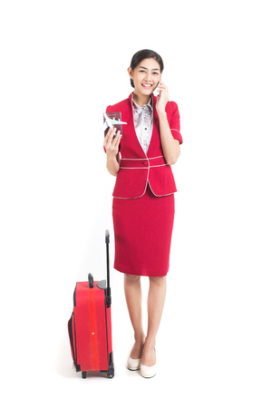 Portrait of Asian Air Hostess using Smartphone for talk, stand and smile isolated on white background
