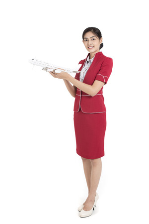 Portrait of Asian Air Hostess holding airplane model and passport, stand and smile at isolated on white background Stockfoto