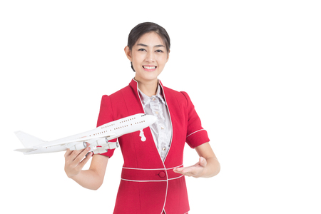 Portrait of Asian Air Hostess holding airplane model and passport stand and smile isolated on white background