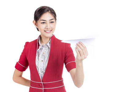 Portrait of Attractive Asian Air Hostess holding paper airplane, stand and smile at isolated on white background