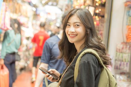 Portrait de femme de voyageur heureux au marché. Femmes asiatiques utilisant un smartphone pour la recherche. Femme avec concept de voyage.