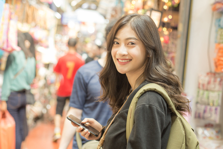 Portrait of Happy Traveler Woman in market. Asian women Using Smartphone for seach Location. Woman with Travel Concept. Archivio Fotografico
