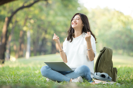 Asian Woman using laptop with attractive smiling at garden. People lifestyle concept.