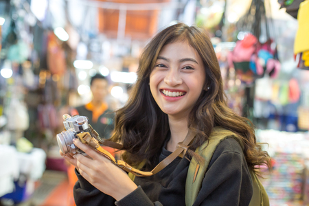 Portrait of Happy Traveler Woman in Market. Asian women Hold Retro Camera for Take Photo, People with Happy emotions. Stock Photo