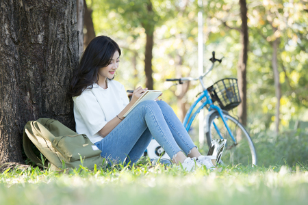 Asian Woman sketch picture on book with attractive smiling at garden. People lifestyle concept. 스톡 콘텐츠