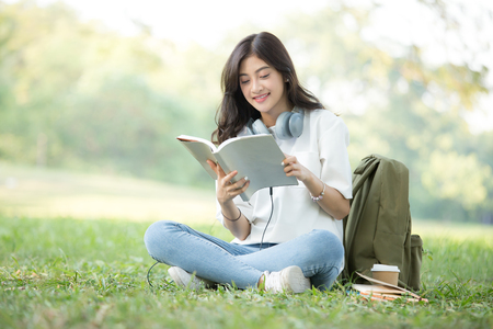 Asian Woman reading book with attractive smiling at garden. People lifestyle concept.