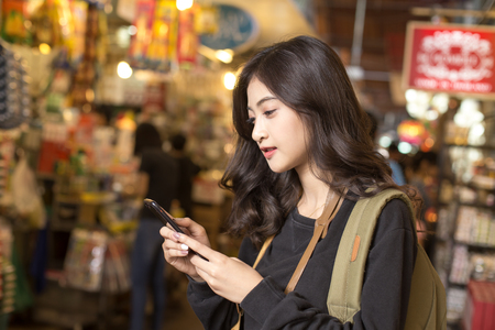 Portrait of Happy Traveler Woman in market. Asian women Using Smartphone for seach Location. Woman with Travel Concept. 스톡 콘텐츠