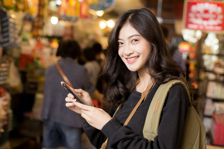 Portrait of Happy Traveler Woman in market. Asian women Using Smartphone for seach Location. Woman with Travel Concept. Banco de Imagens