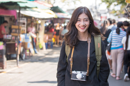 Portrait of Happy Traveler Woman in Market. Asian women Hold Retro Camera for Take Photo, People with Happy emotions. 스톡 콘텐츠