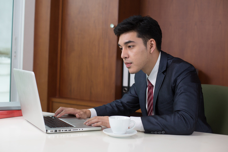 Asian Young Businessman working at office, Businessman using Laptop for work, People working concept.