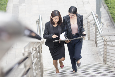 Business people talking for business plan while walking. Woman walking concept. 20-30 year old. Stockfoto