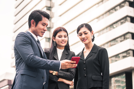 Happy Asian Businesspeople interesting for Present Project by Smartphone with Businessman. People Working at outdoor place. Woman use Smartphone for Working Concept. vintage tone.
