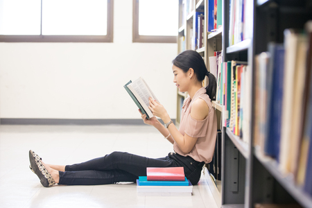 Asian Woman Reading a Book with Smiling at library, Woman with Education Concept.