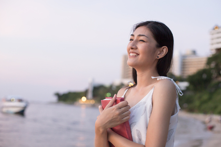 Asain Woman Holding Book at Beach, Woman Holding book with Attractive Smiling.