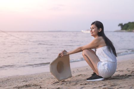 Asain Woman sitting at Beach with Attractive Smiling. Stock Photo