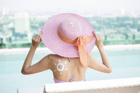 Back of woman with sun symbol at pool.