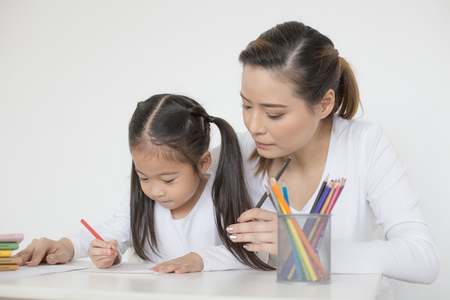 Attractive Little Girl writing Book. Mom Teaching her at home. Children Lifestyle, Education Concept. Stock Photo