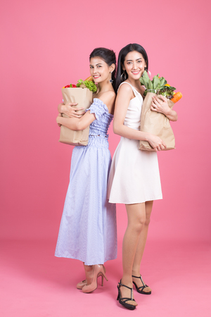 Happy two asian woman holding groceries bag. isolated on pink background. People with shopping concept.