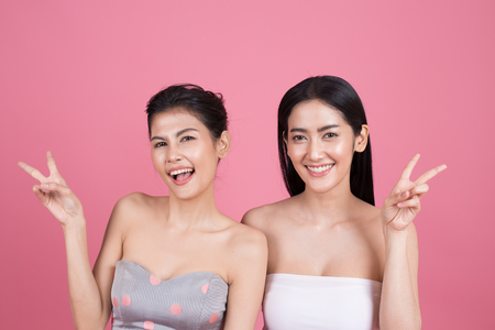 Portrait of Two Beautiful Asian Woman Portrait. Beautiful Woman looking to camera.  People with Youth and Skin Care Concept. isolated on pink background. Stock Photo