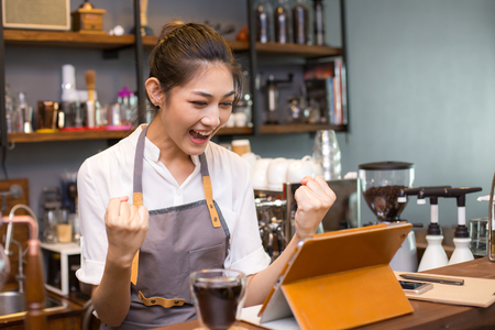 Asian barista woman using tablet for promote shop. Woman success for online marketing.