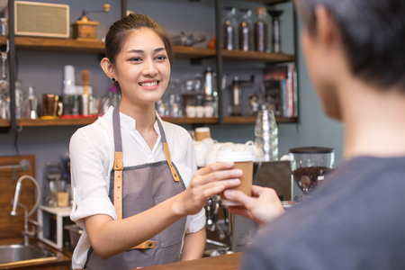 Asian barista woman working at cafe. Woman receive order from customer with attractive smiling.