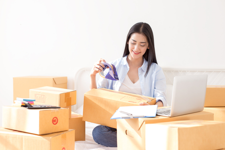 Young asian woman business owner work and white down address for deliver at home, woman business owner concept, 20-25 year old. Banque d'images