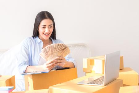 Die junge Asiatin, die zu Hause, junge Inhaber-Frau arbeitet, beginnen für Geschäft online. Leute mit online kaufendem KMU-Unternehmer oder freiberuflichem Arbeitskonzept.