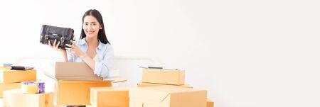 Joven mujer asiática empacando zapatos a la caja, joven propietaria mujer puesta en marcha para negocios en línea. Las personas con compras en línea PYME empresario o concepto de trabajo independiente. Tamaño de la bandera