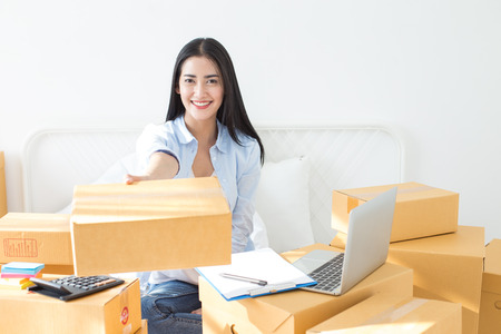 Young asian woman business owner work and white down address for deliver at home, woman business owner concept, 20-25 year old. 스톡 콘텐츠
