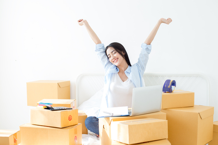 Young Asian Woman relax while work at home, Young Owner Woman Start up for Business Online. People with online shopping SME entrepreneur or freelance working concept.
