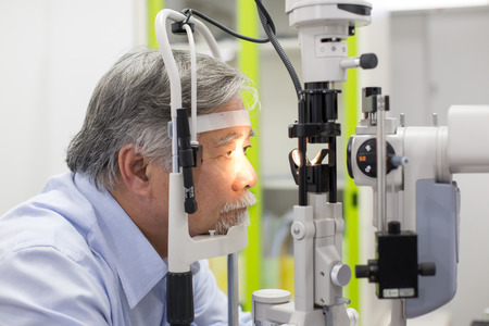 Asian senior male patient having him eyes examined by laser machine. Doctoroptometry concept.